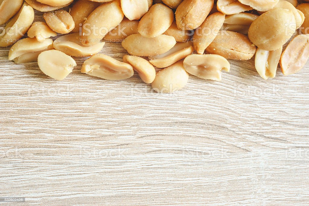 Peeled salted peanuts on wooden background stock photo