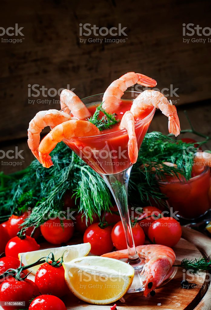 Peeled shrimp with tomato sauce in a martini glass stock photo