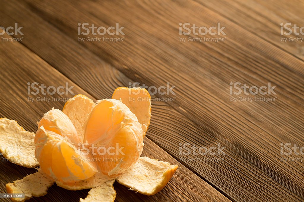 Peeled tangerine on a wooden table. Copy space. stock photo