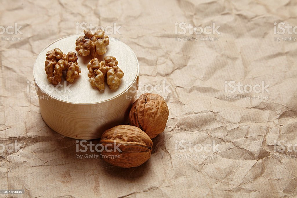 Peeled walnut with whole walnut side view craft brown paper stock photo