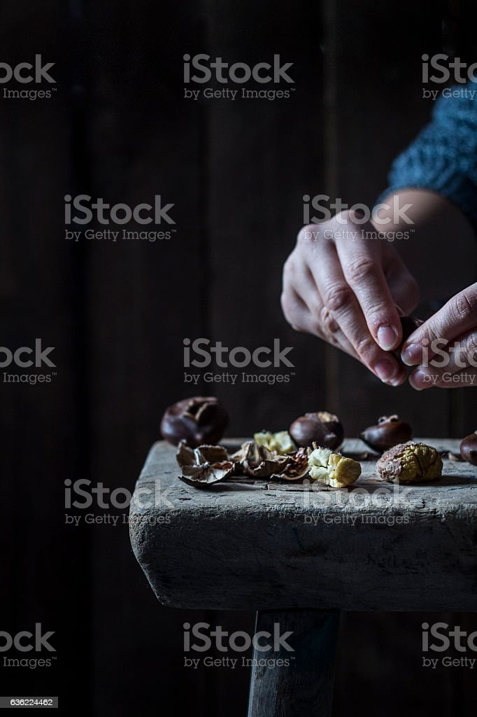 Peeling baked chestnuts on a rustic wood stool stock photo