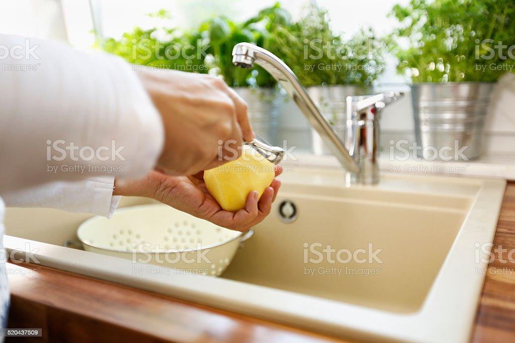 Peeling Fresh Potatoes for Preparing a Healthy Meal stock photo