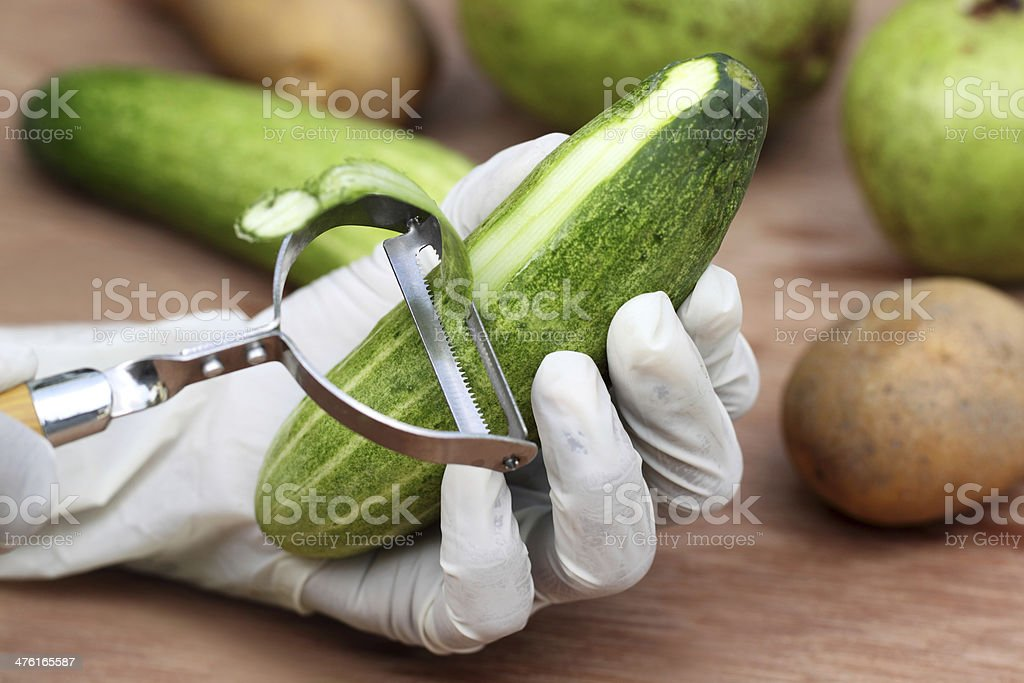 Peeling off the cucumber stock photo