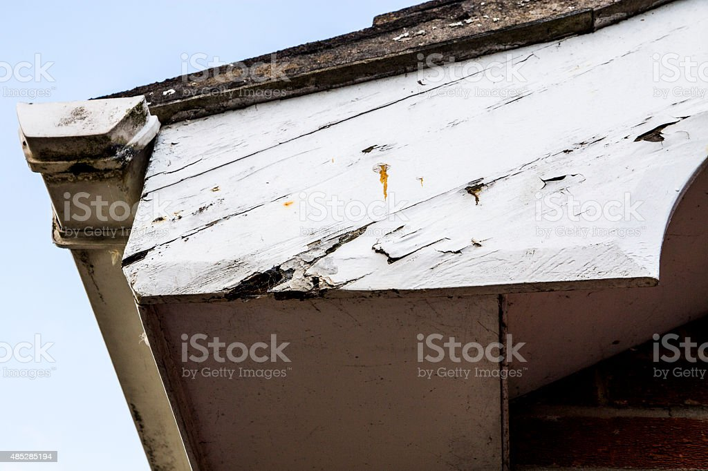 Peeling paint and rotting woodwork around house gutter and fascias royalty-free stock photo