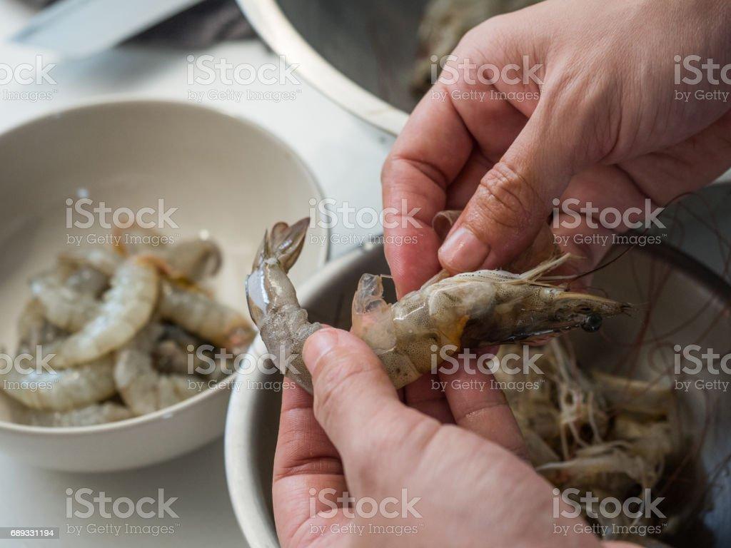 peeling raw shrimp stock photo