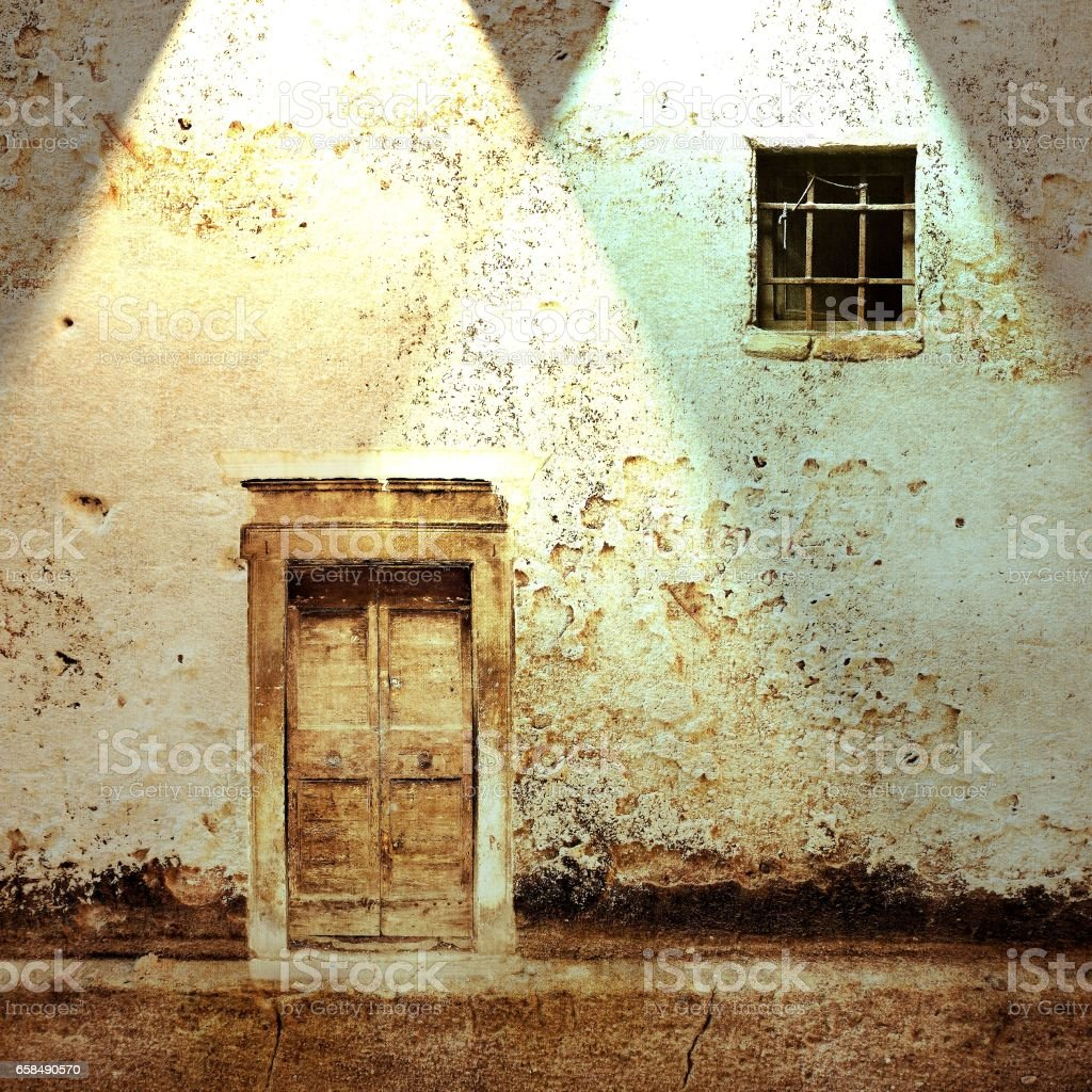 Peeling wall with ancient door and small window. Vintage filter effect. stock photo