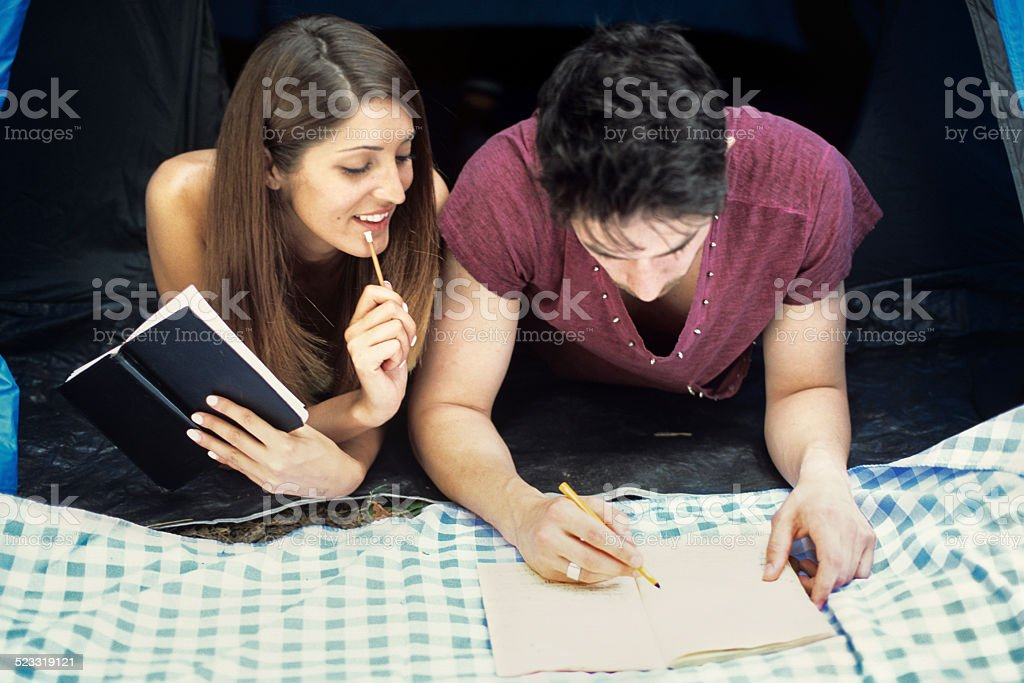 Peeping at the boyfriend's diary - Writing and studying together stock photo