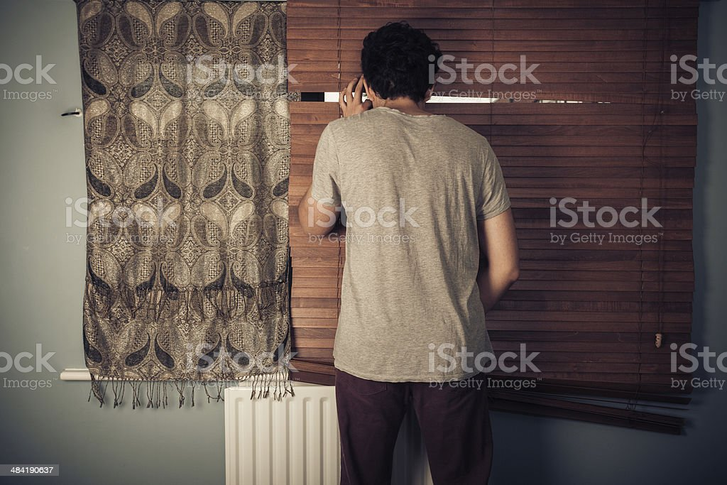 Peeping tom looking through blinds stock photo