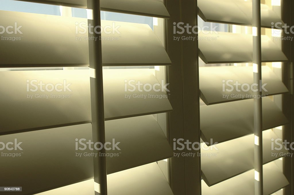 peering out shutters stock photo