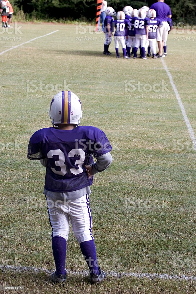 Peewee Football Player Watching Team from Sideline royalty-free stock photo