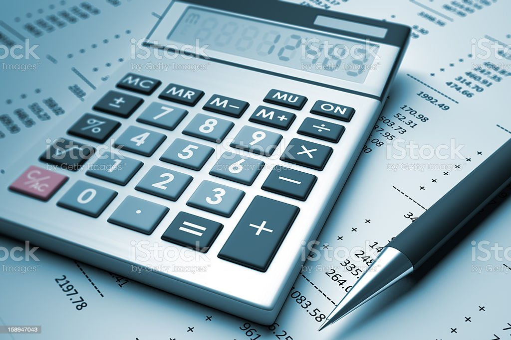 A pen and a calculator sit on a page with numbers royalty-free stock photo