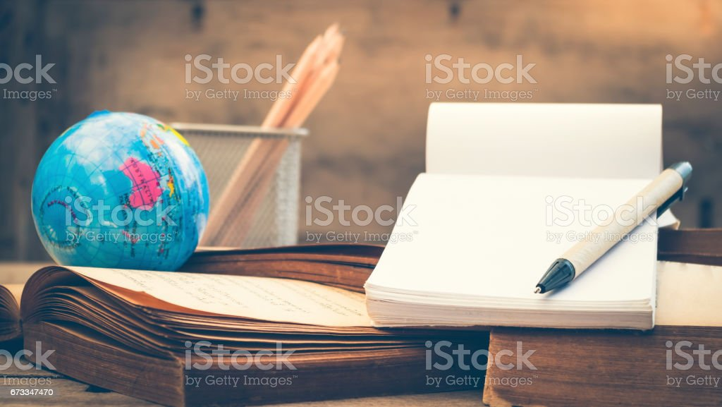 Pen and blank notebook on old book stack, split toning effect stock photo