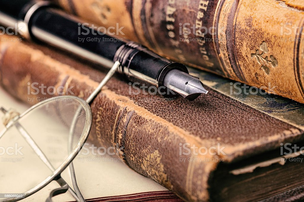 Pen and books with old glasses stock photo