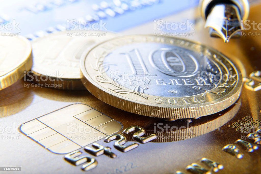 pen and coins on a bank card stock photo