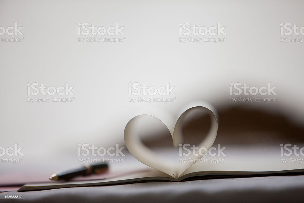 Pen and pages of notebook forming heart-shape royalty-free stock photo