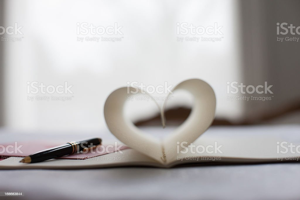 Pen and pages of notebook forming heart-shape stock photo