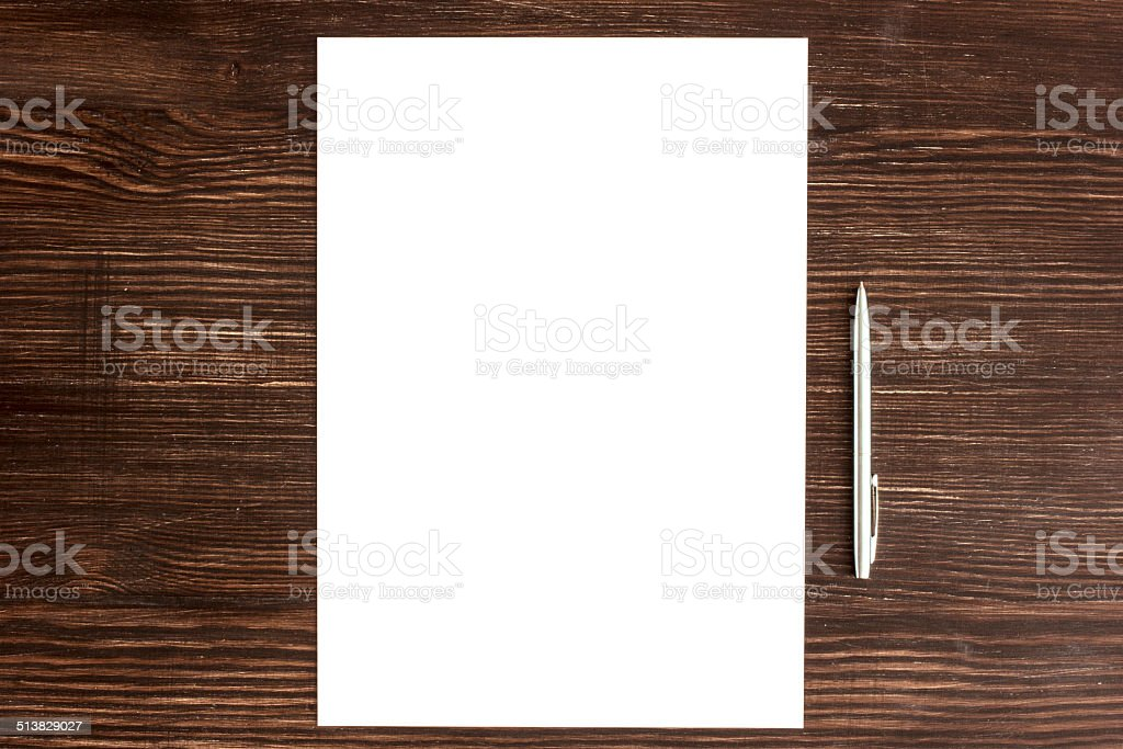 Pen and white card on wooden desk stock photo