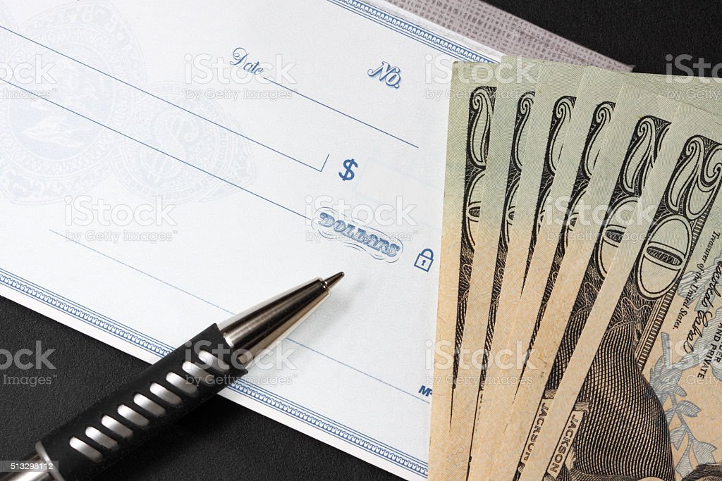 Pen, blank check and  twenty dollar bills stock photo