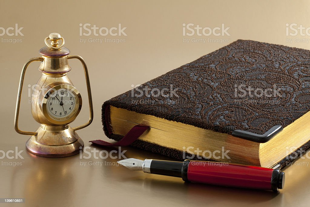 Pen, bronze clock and notepad royalty-free stock photo
