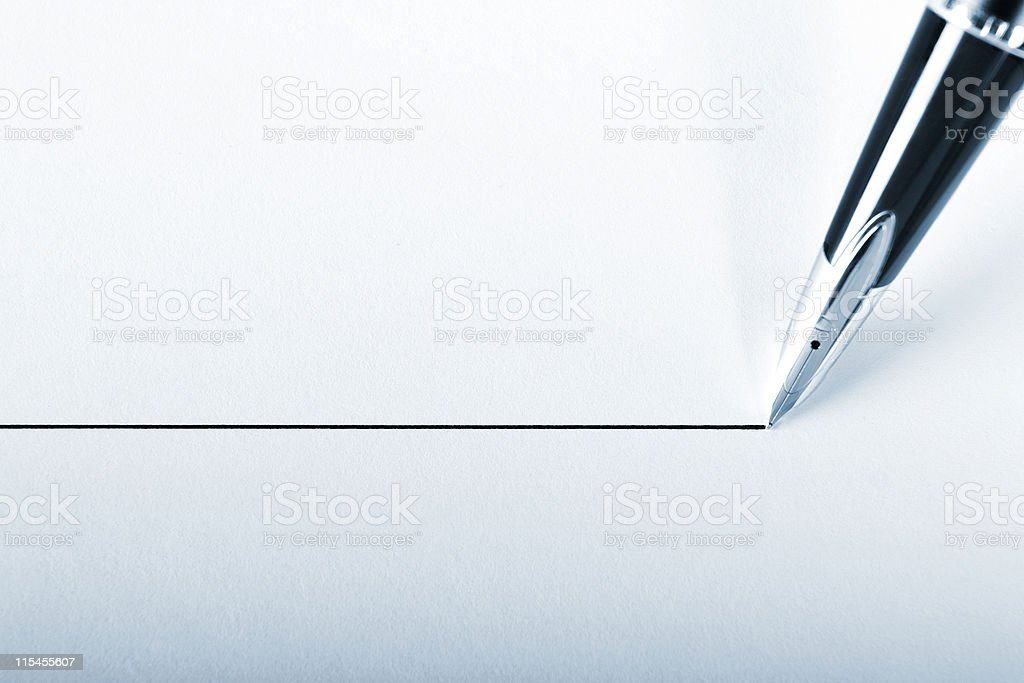 A pen drawing a precision point line on white paper stock photo