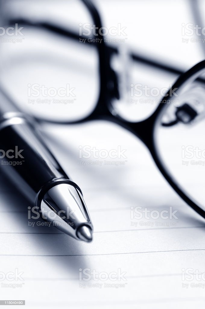 Pen, Eyeglasses, and Notebook Paper Close-Up royalty-free stock photo