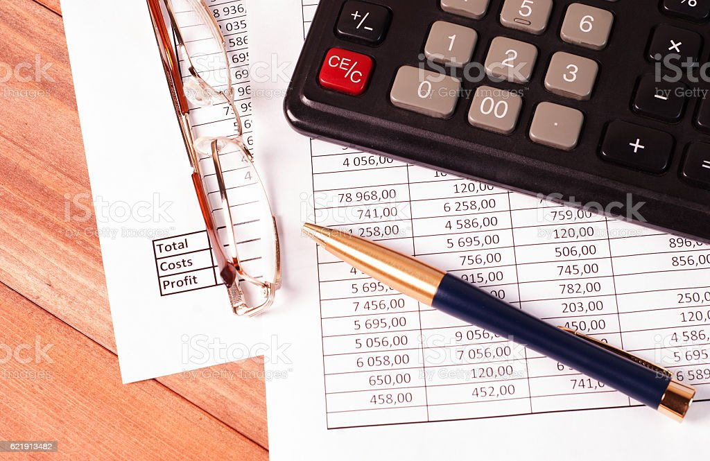 Pen, glasses and calculator on paper tables with numbers stock photo