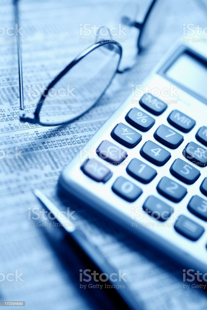 Pen glasses and calculator representing stock market data stock photo