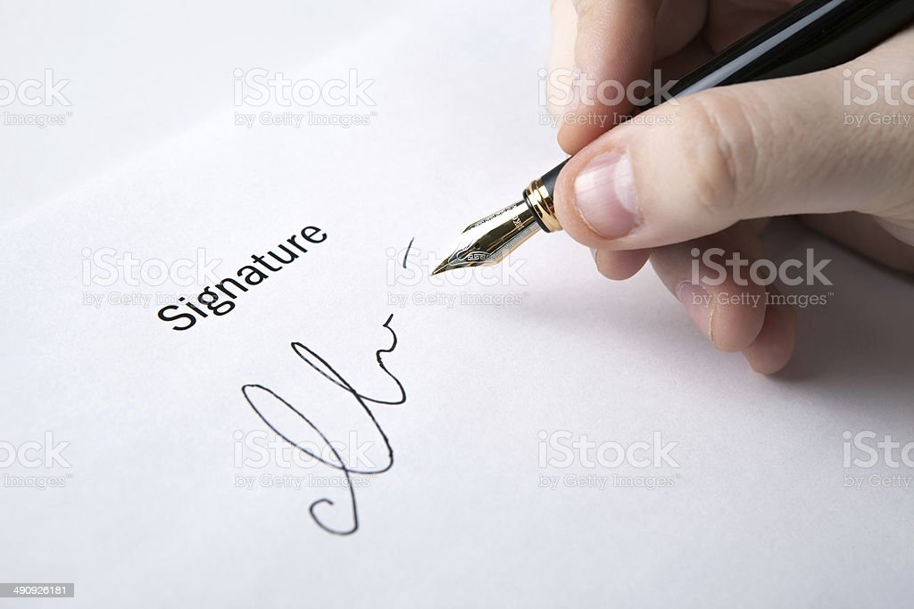 pen in the man's hand and signature stock photo