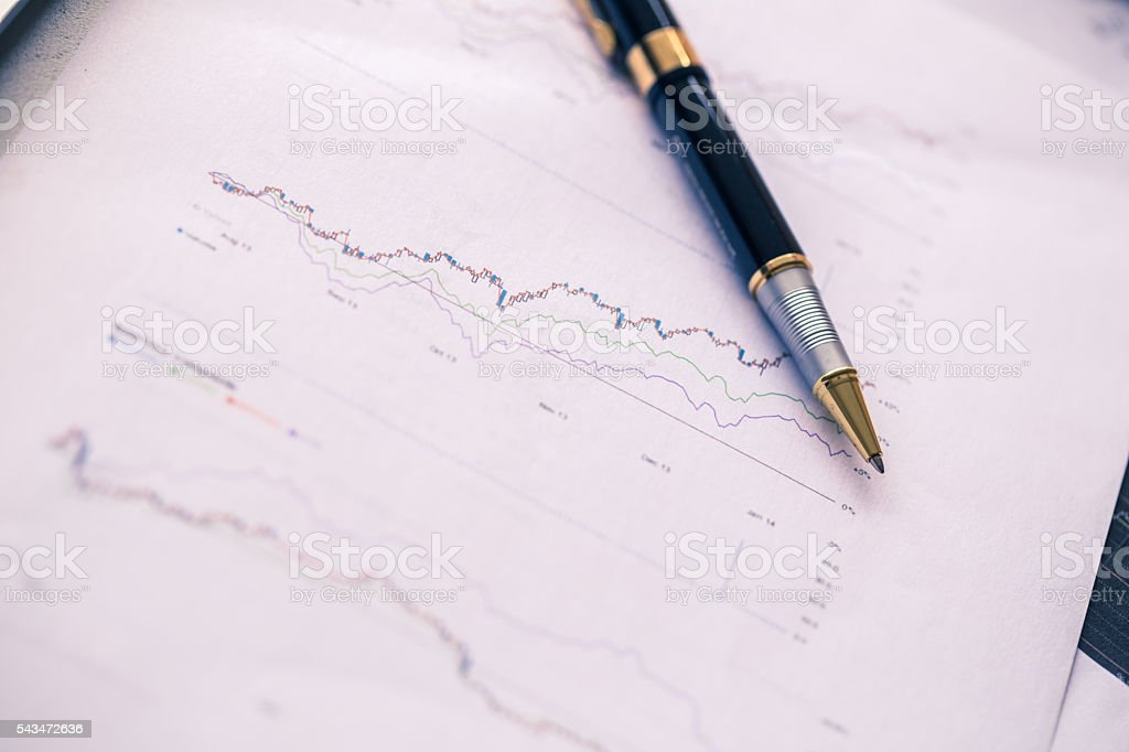 pen on financial report document with stock graph stock photo
