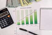 Pen on graphs business report with money
