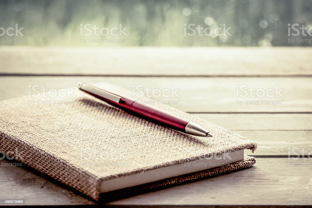 Pen on notebook on wooden table stock photo