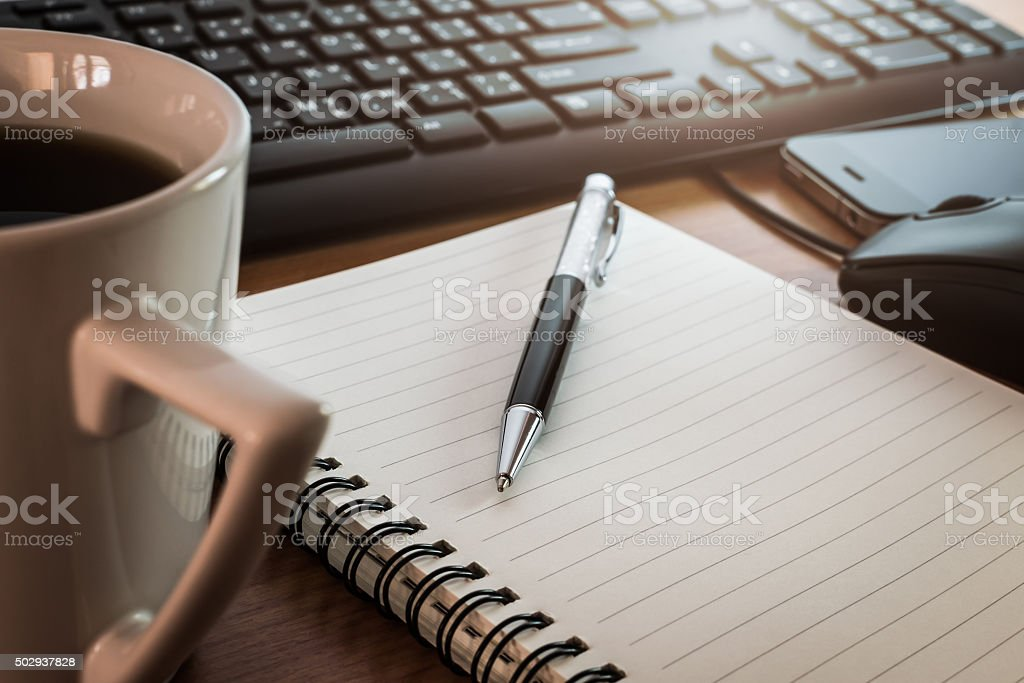 Pen on notebook with coffee computer keyboard, mouse and cell phone...
