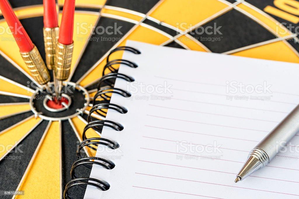pen on notebook with darts on bullseye background stock photo