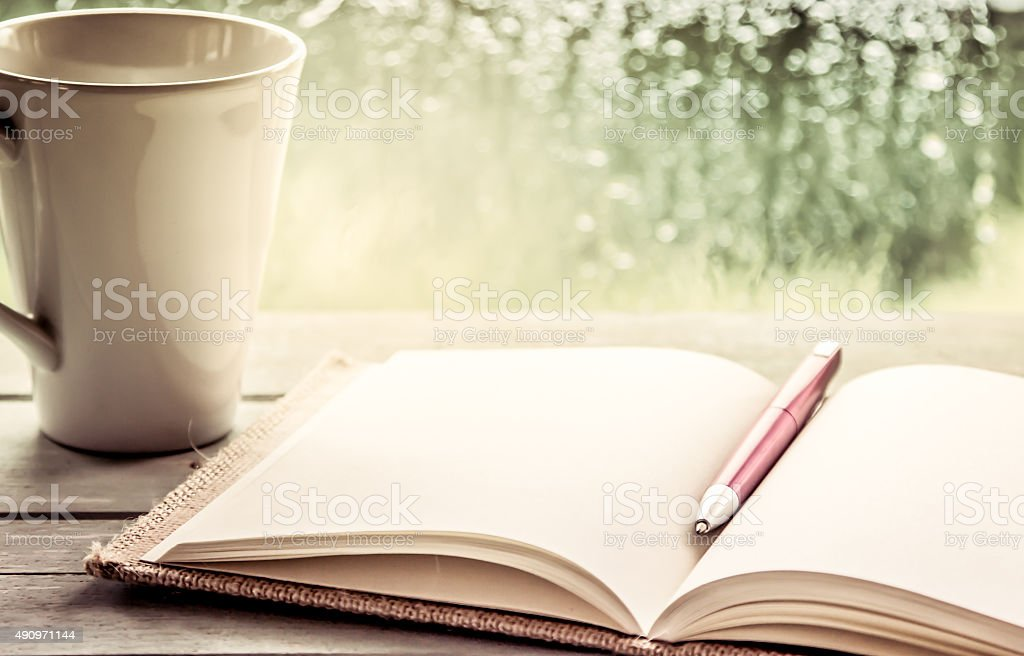 Pen on open notebook and coffee cup stock photo