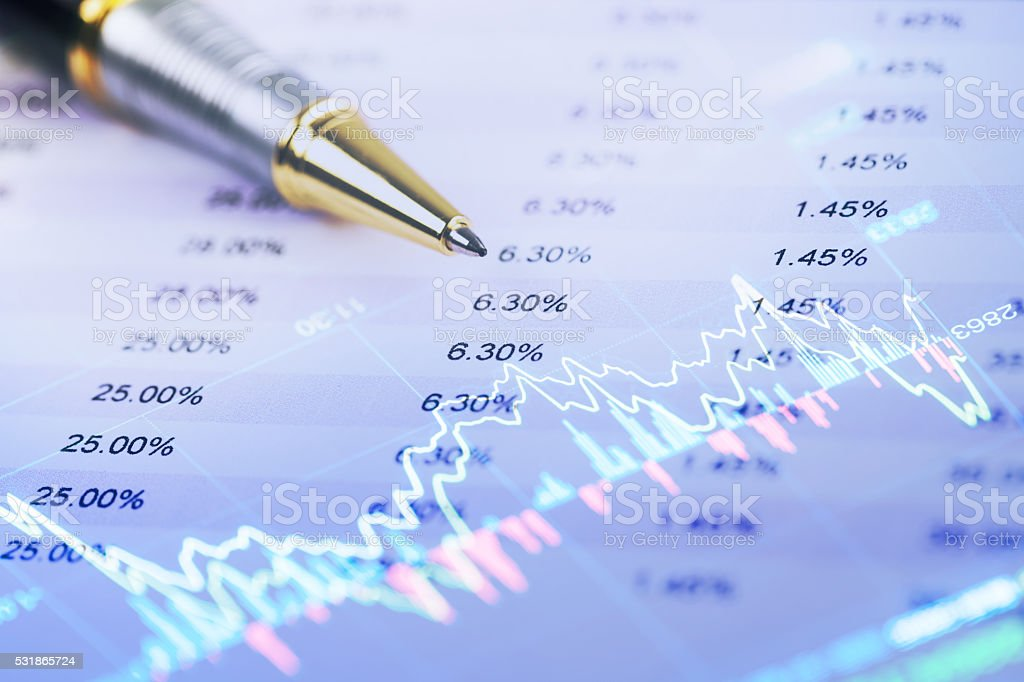 pen on spread sheet data with stock graph stock photo