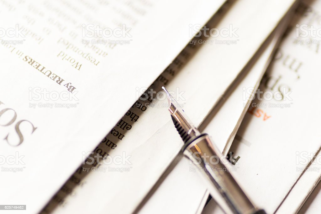 Pen on stack of newspaper stock photo