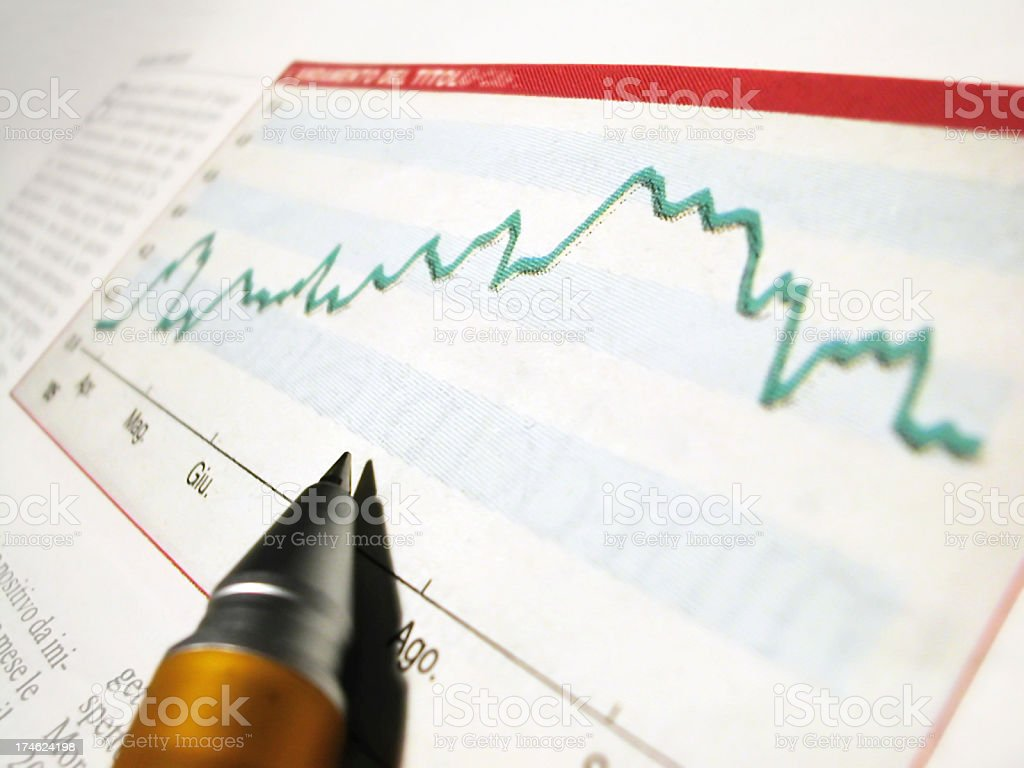 Pen tip on a magazine showing graph of economy growth royalty-free stock photo