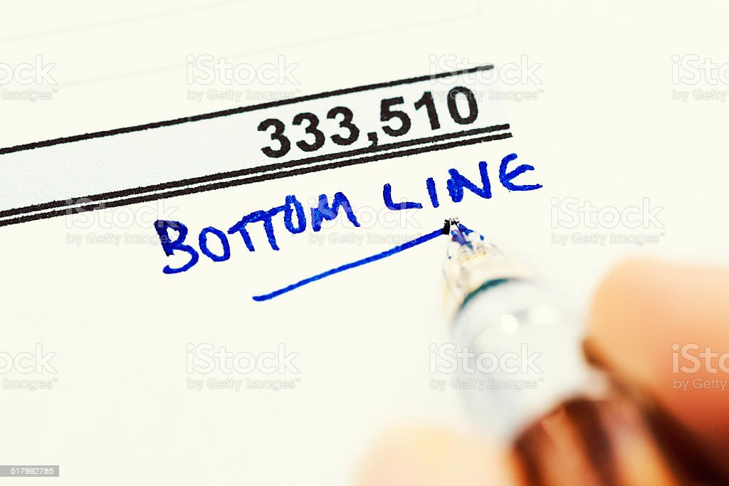 Pen writes 'Bottom line' at base of financial document stock photo