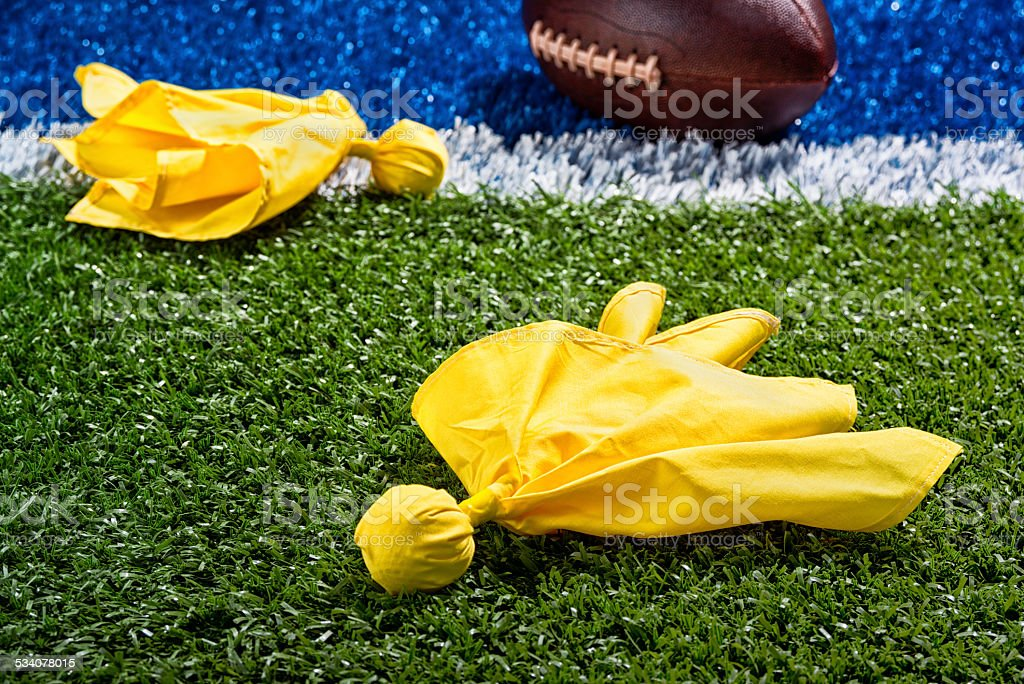 Penalty Flags around a football at the end zone. stock photo