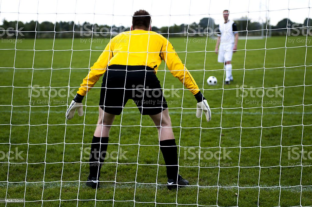 Penalty shoot out with rear view of the goalkeeper royalty-free stock photo