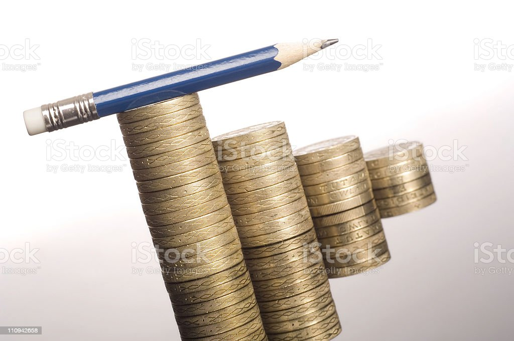 Pencil and pound coins money stock photo