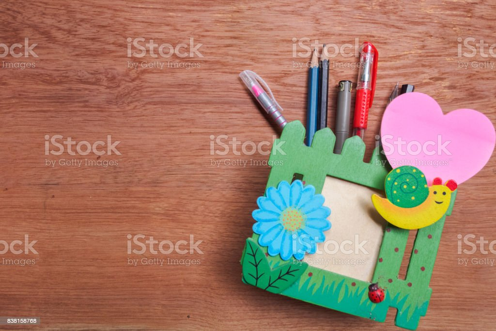 Pencil box and paper clip on wooden table stock photo