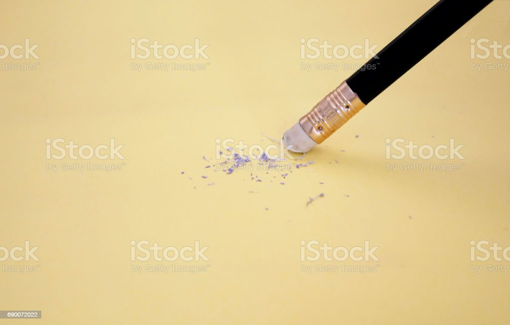 Pencil eraser removing a written mistake on a piece of paper, delete,...