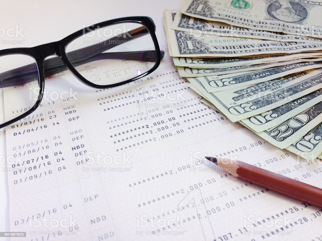 Pencil, eyeglasses, money and savings account passbook or financial statement on white background stock photo