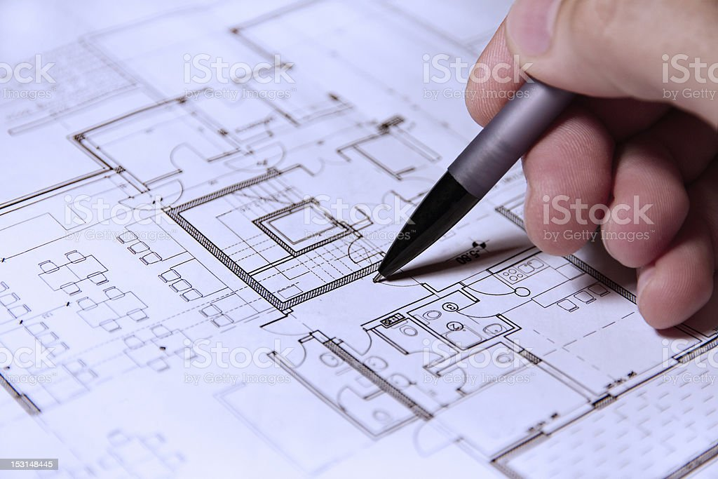 Pencil in hand on building plans royalty-free stock photo