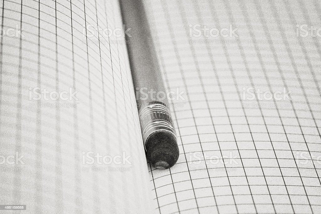 Pencil liying in a blank open squared notebook - abstract stock photo