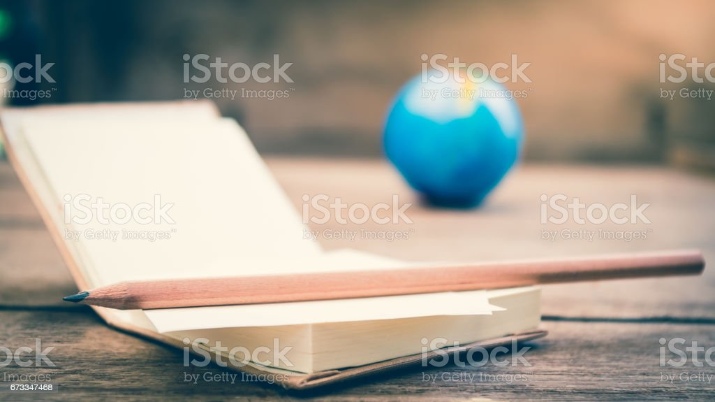 Pencil place on blank notebook with small globe as blur background, select focus and split toning effect stock photo