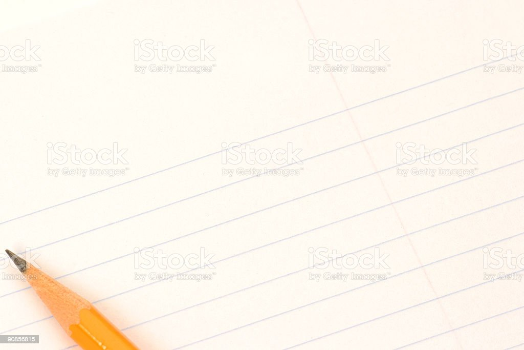 A pencil resting on a piece of loose leaf paper stock photo