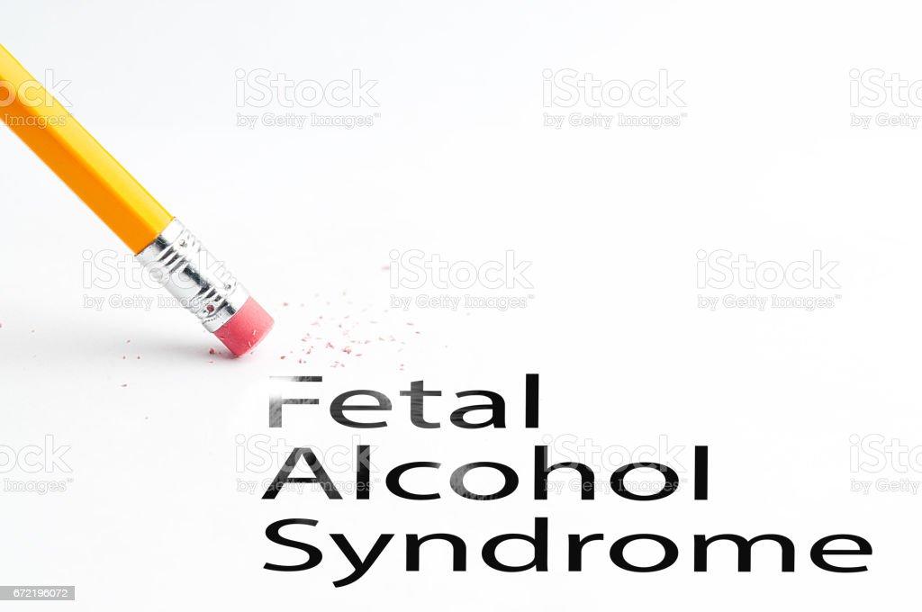 Closeup of pencil eraser and black fetal alcohol syndrome text. Fetal...