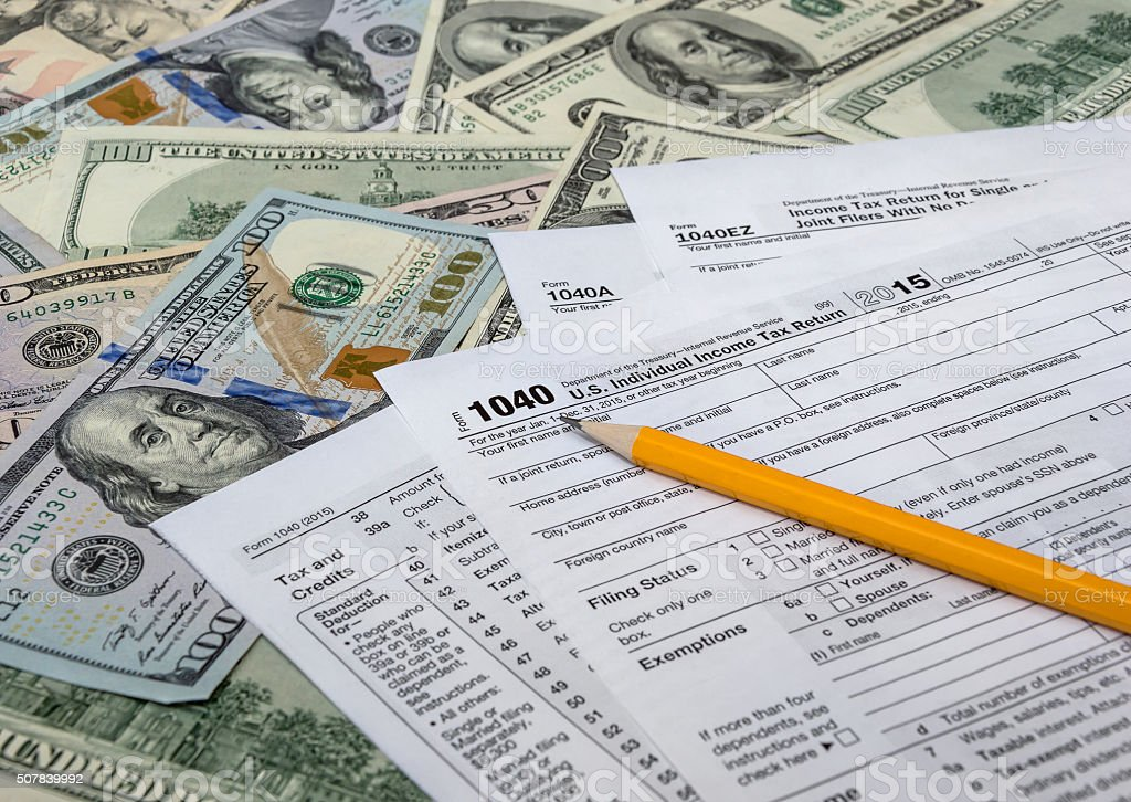 Pencil with tax form on US dollarbills background stock photo